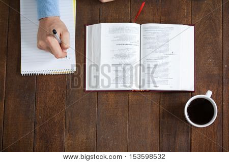 Man sitting at desk with a bible and cup of coffee while writing on notepad