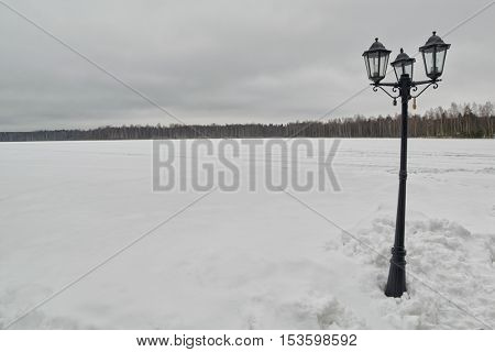Abstract picture with street lantern on a winter frozen lake covered with snow