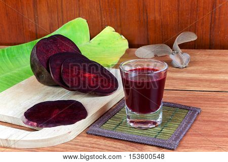 Fresh slices red beet root and beet root fruit juice in shot glass a wood background