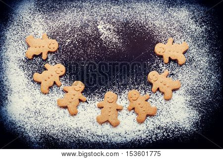 Gingerbread Men With Christmas In Dance On Dark Table
