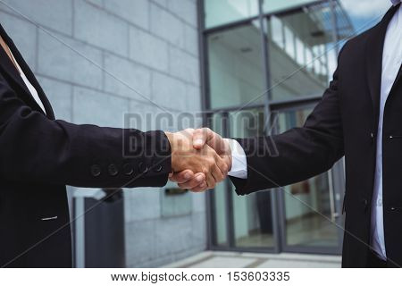 Mid-section of businesspeople shaking hands in office building