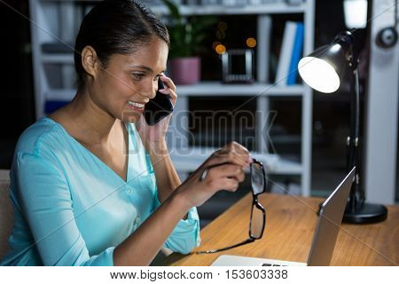 Businesswoman talking on mobile phone while working in office at night