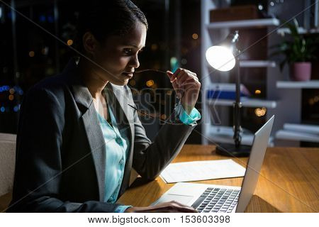 Businesswoman working on laptop in office at night
