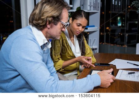 Business executives discussing over digital tablet in office at night