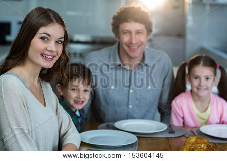 Portrait of happy family sitting on a dinning table in kitchen