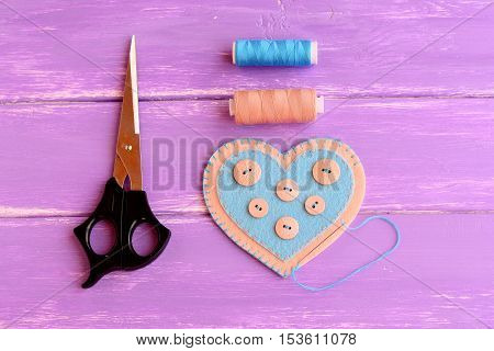 How to make a felt heart crafts. Step. Join the felt edges of felt heart with blue thread. Scissors, thread, needle on wooden background. Crafts idea for Valentine's day, wedding, mother's day