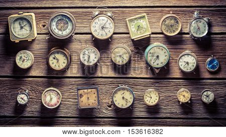 Many aged clocks on old wooden wall
