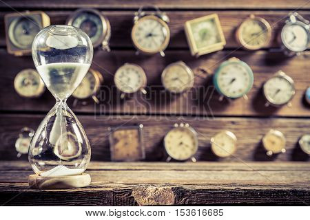 Old hourglass as the old way of timing on old wooden table