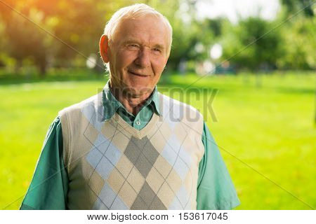Senior man is smiling. Elderly male on nature background. Veteran of labor. Wise mind and modest smile.