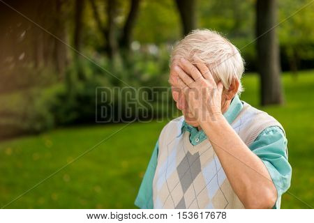 Senior man touching his forehead. Elderly male outdoors. Sad and lonely. I was wrong.