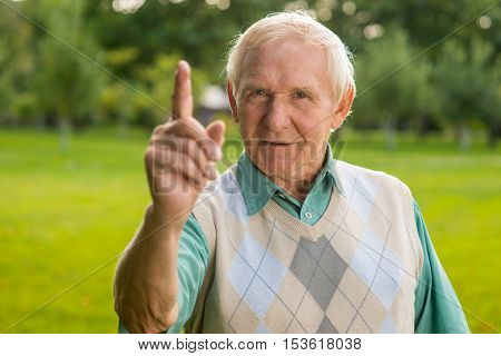 Man with raised finger. Old male looking at camera. Remember what I've taught you. Important lesson in life.