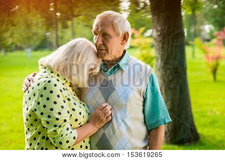 Woman leaning on man's shoulder. Old couple outdoor. How to settle a conflict. Trust and understanding.