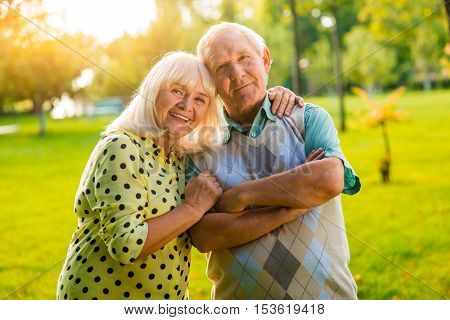 Senior woman hugs man. Couple looking at the camera. Hearts united by love. Support and trust are priceless.