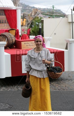 FUNCHAL MADEIRA PORTUGAL - SEPTEMBER 4 2016: the woman carry the basket of grapes in traditional costume. Madeira Wine Festival - Historical and Ethnographic parade in Funchal on Madeira. Portugal