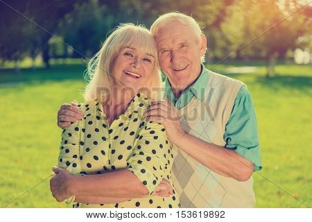 Older couple outdoor. Two people smiling. Happiness given by fate. Let the sun shine brighter.