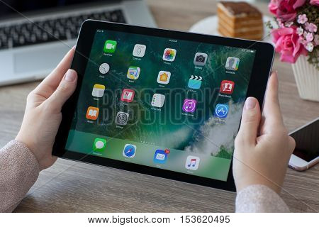 Alushta Russia - October 9 2016: Woman holding in the hand a iPad Pro Space Gray with wallpaper IOS 10 in the screen. iPad Pro was created and developed by the Apple inc.