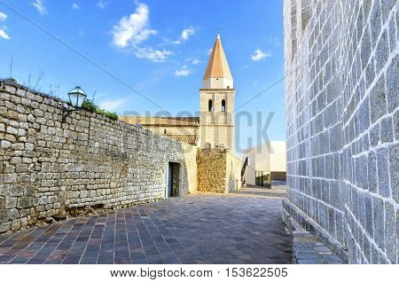 The pyramidal tower of the Church of our Lady of Health a romanesque cathedral formely named St Michael the archangel basilica at the Square of the The Glagolitic housed monasteries on Krk island in Croatia and the elementary school mirrors.