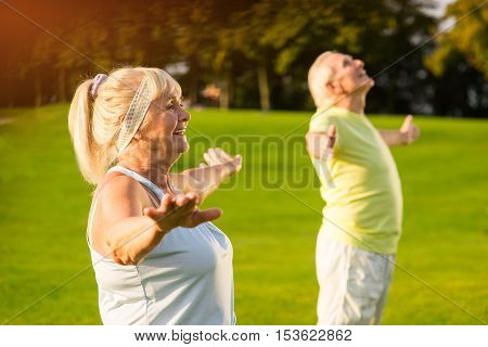 Senior woman with outstretched arms. Smiling lady and man outdoors. Gymnastics improves health. Happy and energetic.