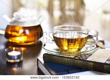 Teatime scene, cup of tea on a book stack with burning candles and selective focus.
