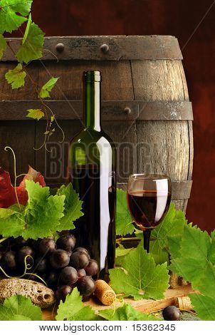 Red wine still life with grapevine and cask