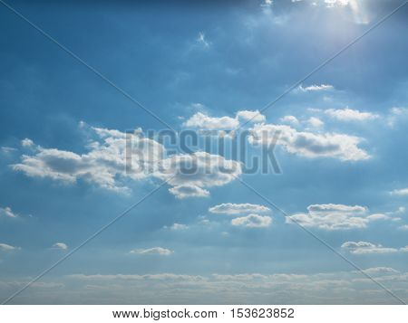 View of the sunlight above the cloudy sky. Picture of the blue sky with beautiful white clouds. The great foto of the white cumulus. Picture of the white cumulus moving through the blue sky.