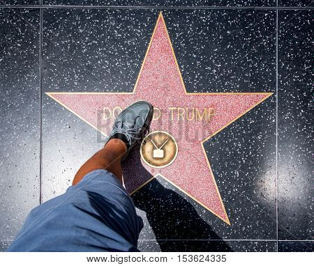 Los Angeles USA - August 5 2016: Man stepping on Donald Trump Star before it was damaged at Walk of Fame on Hollywood Boulevard Los Angeles on August 5th 2016.