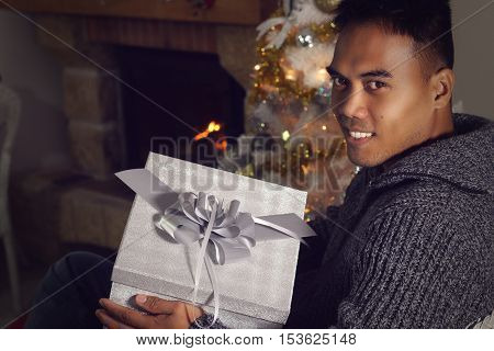 Young Filipino holding a Christmas present at home