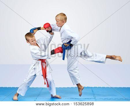 In karategi two karateka are training punch arm and block