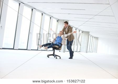 Young businessman pushing female colleague in chair at empty office