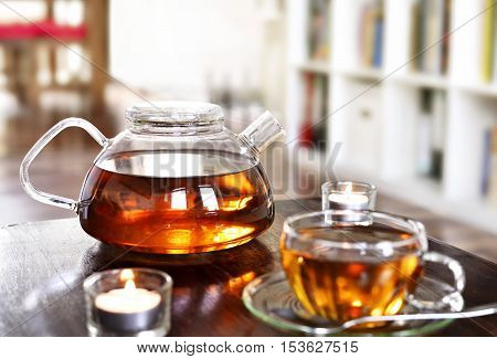 Teatime scene, cup of tea and teapot with burning candles and selective focus.