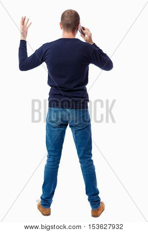Back view of  pointing young men talking on cell phone. Young guy  gesture. Rear view people collection.  backside view of person.  guy in a black sweater a hand gesturing while talking on the phone.