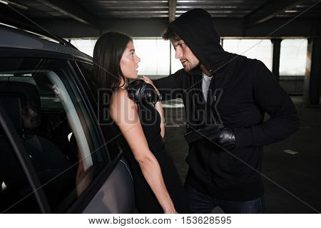 Criminal man in black hoodie standing and threatening with gun to businesswoman near the car