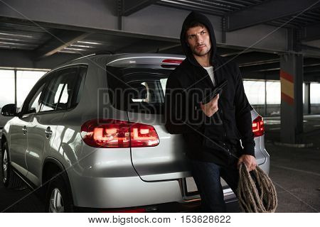 Criminal young man holding gun and rope near the car on parking