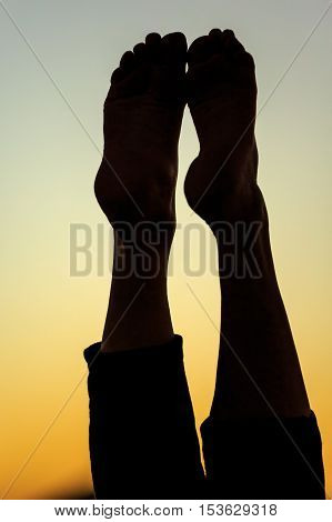 Silhouette legs of meditating woman in front of the red sinking sun on desert