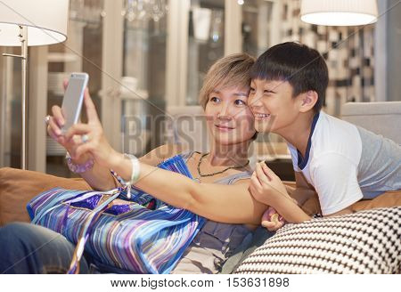 Mother And Son Posing For Selfie On Sofa