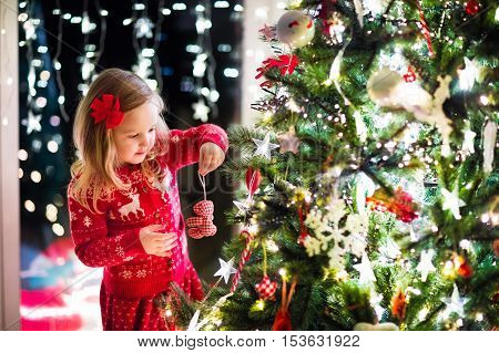 Little girl in red knitted Nordic reindeer sweater hanging ornaments on Christmas tree with light bauble and candy canes. Child decorating Xmas tree in beautiful family living room with fireplace.