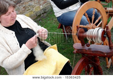 RATIBORICE, CZECH REPUBLIC - APRIL 24:  Older woman spinning wool on traditional spinning wheel - The Shepherds Festival 2010, chateau area on April 24, 2010 in Ratiborice, Czech Republic