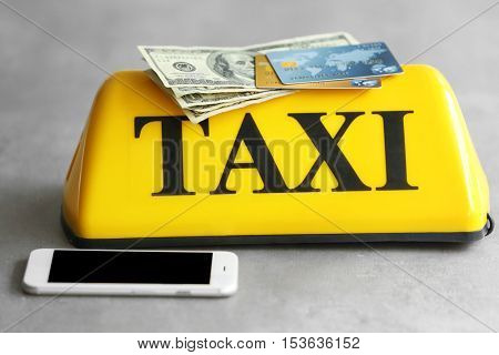 Yellow taxi roof sign with phone, credit cards and American dollars on gray background, closeup