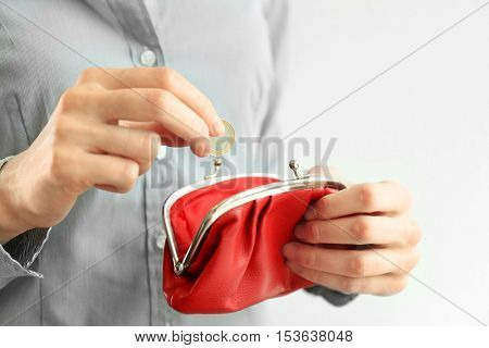 Woman putting coin into red purse