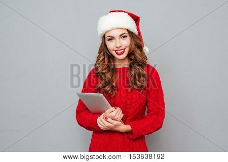 Happy attractive girl in santa claus hat standing and holding tablet over gray background