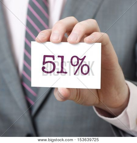 51% written on a card held by a businessman