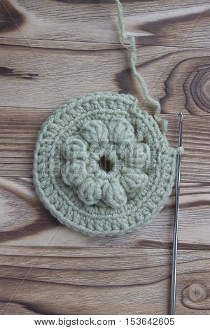 The beginning of handmade crocheted cotton organic doily coaster or napkin on wooden background. Old metal crocheting hook