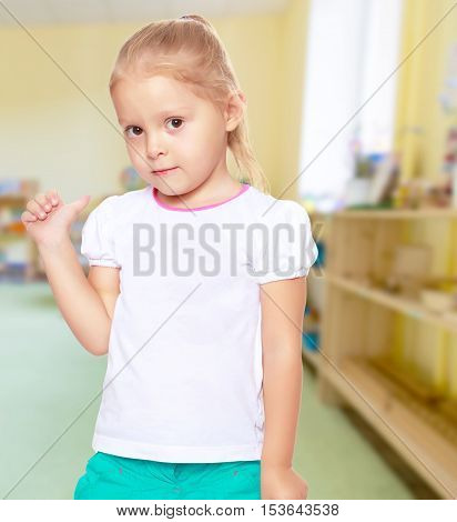 The concept of pre-school education. Montessori.Cute little blond girl in white tank top without a pattern.Girl shows thumb to the side.