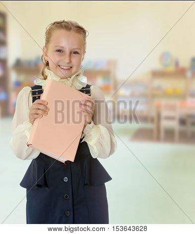 Happy girl schoolgirl in black dress and white blouse holding a textbook and smiling cheerfully at the camera. Close-up.In the Montessori room the children's garden