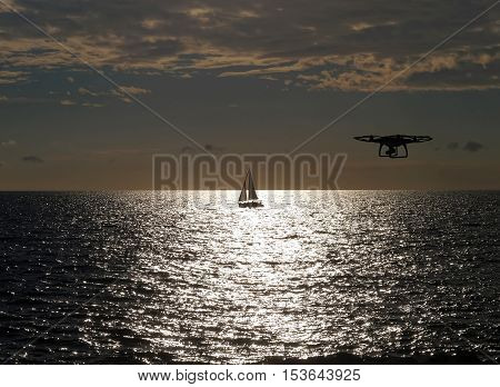 remote controlled drone flying above sea at sunset
