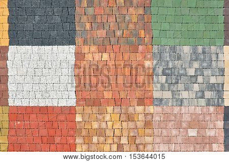 Urban background. Samples of trapezoidal pavement tiles of red black white gray green.