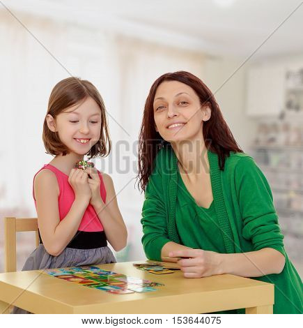 Joyful little girl and her mother at the table laid out cards with pictures.In the children's room where there are shelves with toys.