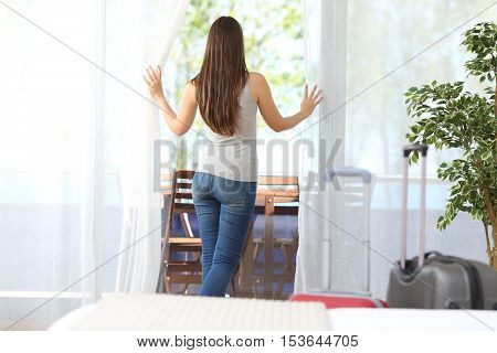 Hotel customer in her room on vacations looking outside through the window