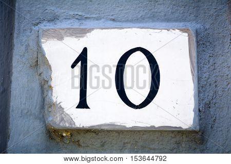 Door number ten sign on plaster wall