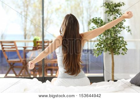 Woman stretching arms and waking up sitting on the bed in an hotel or home bedroom looking the sea outdoors through the window